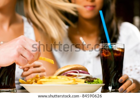 Two women - one is African American - eating hamburger and drinking soda in a fast food diner; focus on the meal - stock photo