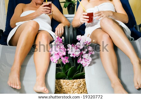 Two women (only torso to be seen) relaxing on beds in a health spa drinking juice - stock photo