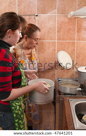 Two women, pans and the gas furnace. - stock photo