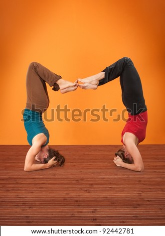 Two women perform Vrisikasana yoga posture on a wooden mat
