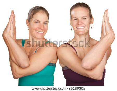 Two women perfrom namaskar with hands twisted - stock photo