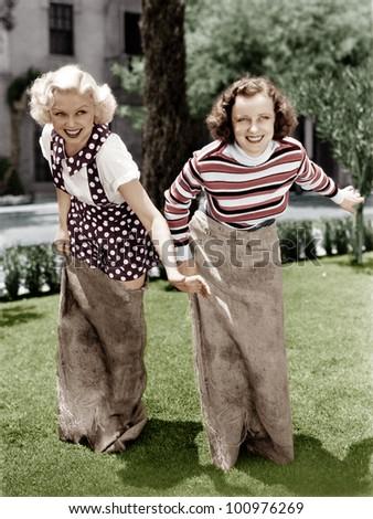 Two women playing a game of potato sack racing - stock photo