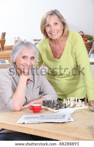 Two women playing an informal game of chess - stock photo