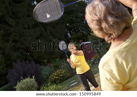 Two women playing badminton in the garden - stock photo