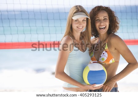 Two women playing beach volleyball - stock photo