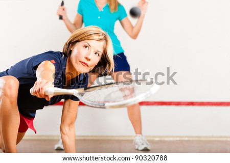 Two women playing squash as racket sport in gym - stock photo