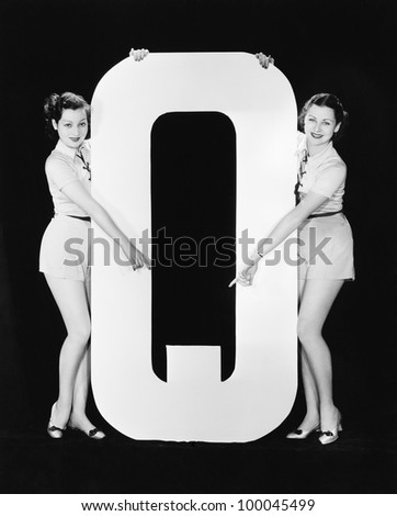 Two women pointing at huge letter Q - stock photo