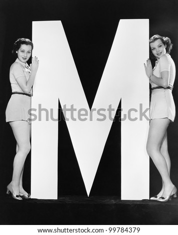 Two women posing with huge letter M - stock photo
