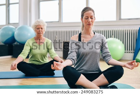 Two women practicing yoga in class. Female trainer and senior woman sitting in lotus position meditating. - stock photo