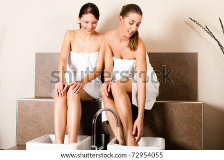 Two women presumably best friends - taking a footbath - stock photo
