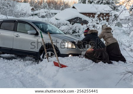 two women pushing a car stuck in the snow - stock photo