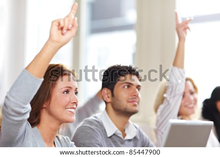 Two women raising hands in university class - stock photo
