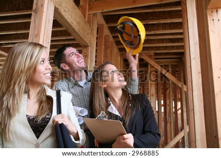 Two women real estate agents celebrating with the construction man - stock photo
