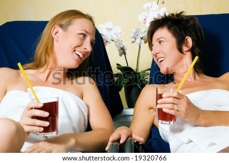 Two women relaxing on beds in a health club drinking juice - stock photo