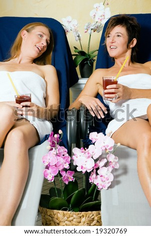 Two women relaxing on beds in a health spa drinking juice - stock photo