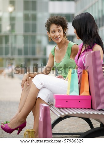 two women relaxing on bench after shopping. Vertical shape, full length, copy space - stock photo