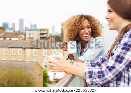 Two Women Relaxing On Rooftop Garden Drinking Coffee - stock photo