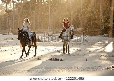 two women riding horseback on the beach - stock photo