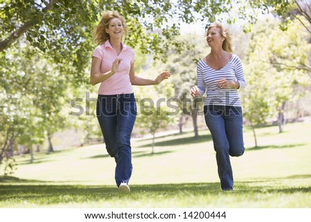 Two women running in park and smiling - stock photo
