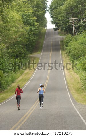 Two women running on rural road - stock photo