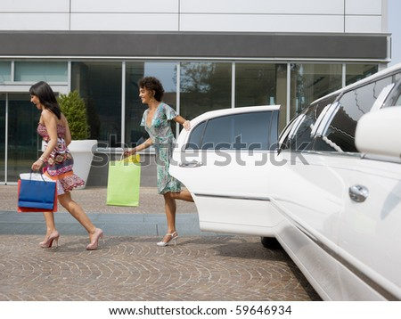 two women running out of limousine with shopping bags. Horizontal shape, full length - stock photo