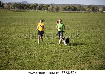 Two women running through a field with a dog. - stock photo