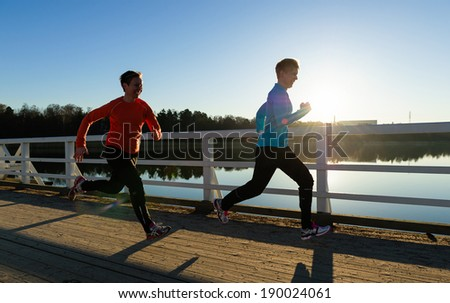 Two women running together along the bridge at sunrise - stock photo
