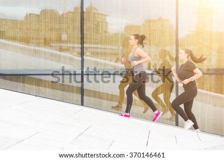 Two women running up a staircase with a big reflecting window on background. They are wearing gray and black sportswear. Healthy lifestyle and sport concepts.