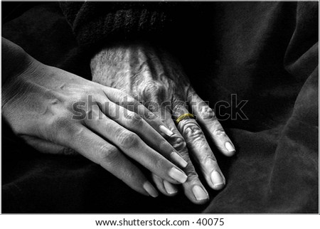 Two women's hands against a neutral backdrop - stock photo