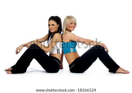 Two women sat back to back in gym clothes