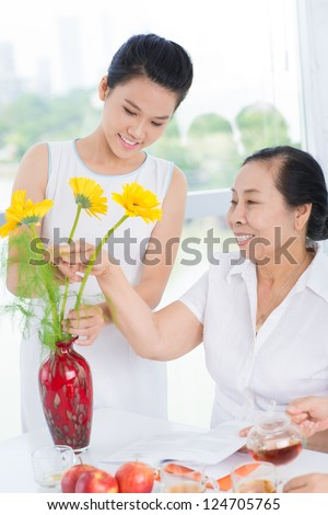 Two women seated at table and busy with flowers