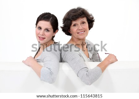 Two women seated in a sofa - stock photo