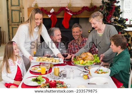 Two women serving christmas dinner to their family at home in the living room - stock photo