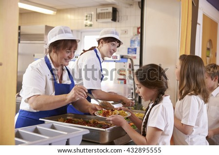 Two women serving food to a girl in a school cafeteria queue - stock photo