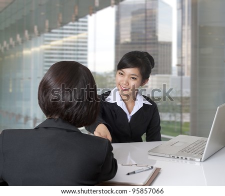 Two women shaking hands in the office - stock photo