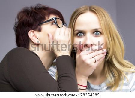 two women sharing a secret - stock photo