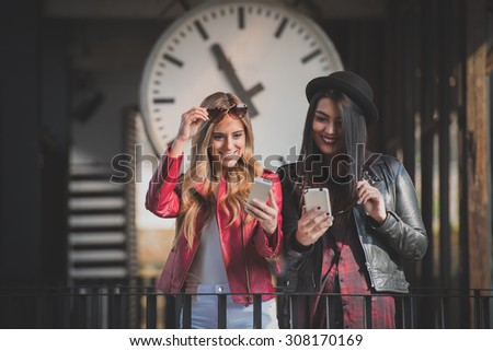 Two women sharing pictures on their smart phones - stock photo