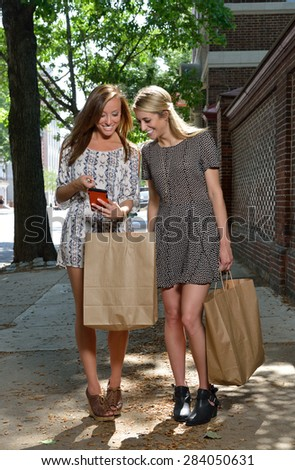 Two women shop together on city street - both carry brown paper shopping bags - looking at cell phone as they walk - stock photo