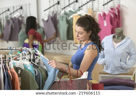 Two women shopping for clothes - stock photo