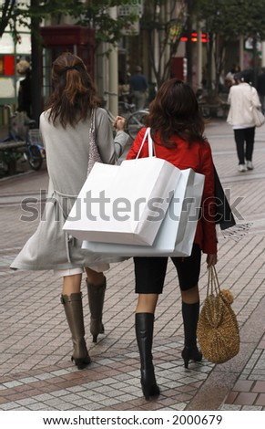 Two women shopping in a city street - stock photo
