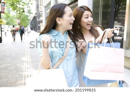Two women shopping in the city - stock photo