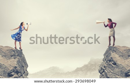 Two women shouting in megaphones at each other - stock photo