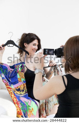 two women showing new clothes and having fun with camcorder - stock photo