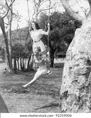 Two women sitting and standing on a swing - stock photo