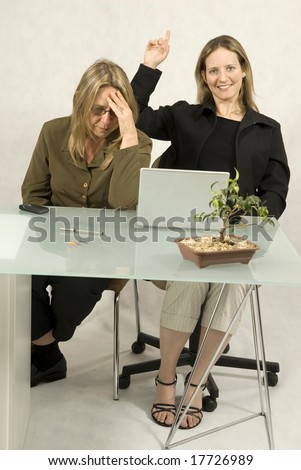 Two women sitting at a desk in front of a computer