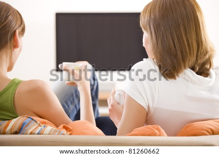 two women sitting in front of monitor watching television - stock photo