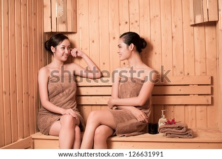 Two women sitting in sauna and talking to each other - stock photo
