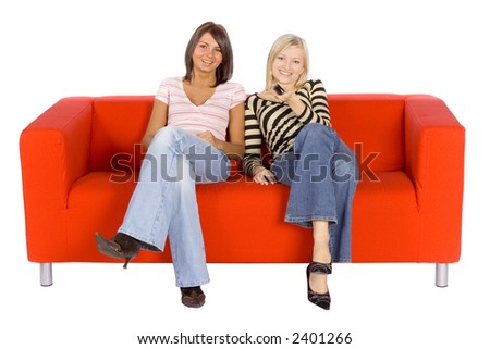 Two women sitting on a red couch with remote control.  Isolated on white background, in studio.