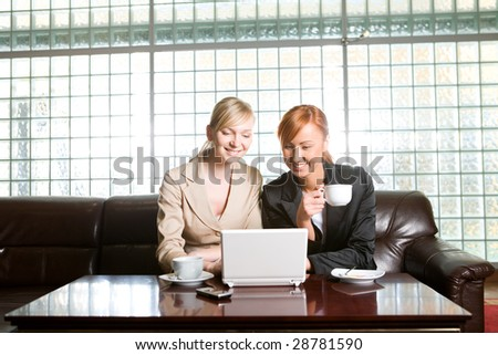 Two women sitting on couch and drinking coffee. They looking something on laptop. - stock photo