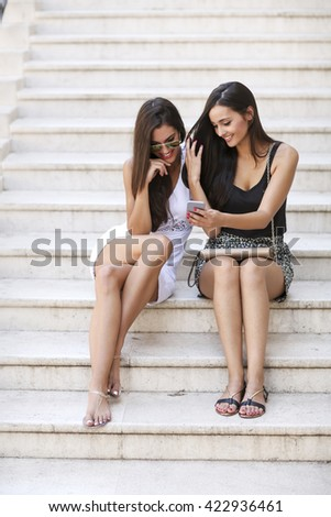 Two women sitting on the stairs and looking at the phone